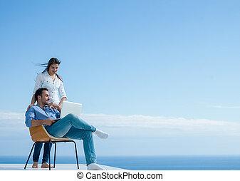 Una pareja relajada trabajando en la computadora portátil en casa