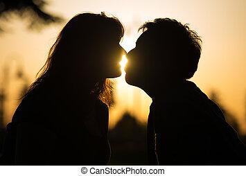 Una pareja romántica besándose al atardecer