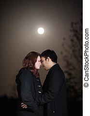 Una pareja romántica en una noche de luna