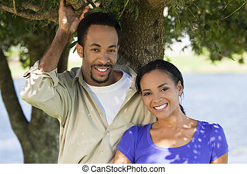 Una pareja romántica feliz de Estados Unidos sonriendo bajo un árbol
