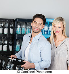 Una pareja saludable atractiva comprando agua embotellada