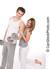 Una pareja sana sonriente ejercitando con pesas