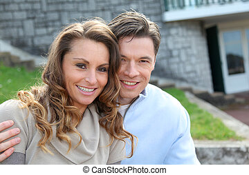 Una pareja sentada frente a su nuevo hogar