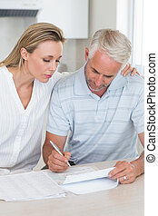 Una pareja seria trabajando en sus finanzas
