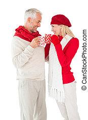 Una pareja sonriente en invierno brindando con tazas