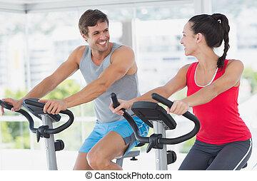 Una pareja sonriente haciendo ejercicio en Spinn