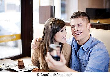 Una pareja tomando fotos en el café