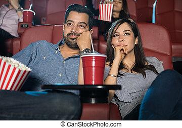 Una pareja viendo una película aburrida
