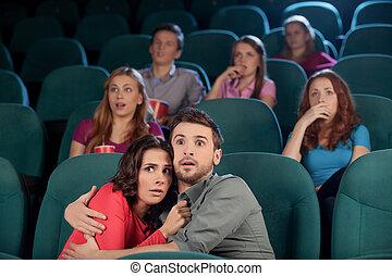 Una película de terror. Una joven pareja aterrorizada abrazando mientras veía la película en el cine