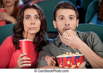 Una película emocionante. Sorprendente pareja de jóvenes comiendo palomitas y bebiendo gaseosa mientras veían la película en el cine