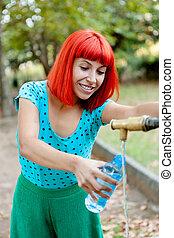 Una pelirroja llenando una botella de agua en una fuente