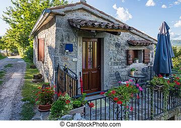 Una pequeña casa de piedra con una cerca de metal