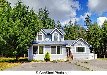 Una pequeña casa gris americana cerca del bosque.