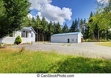 Una pequeña casa gris con taller y un gran estacionamiento.