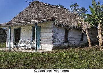 Una pequeña casa residencial en Cuba con mecedoras