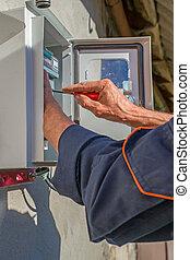 Una persona trabajando en la instalación de equipos de medidor eléctrico.