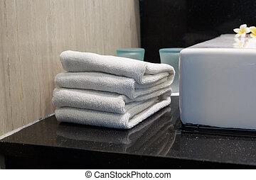 Una pila de toallas blancas en un primer plano del baño de un hotel