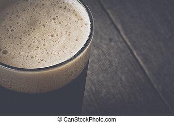 Una pinta de cerveza oscura en el fondo de madera con estilo de película vintage