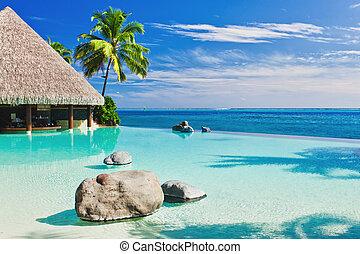 Una piscina infinita con palmera sobre el océano
