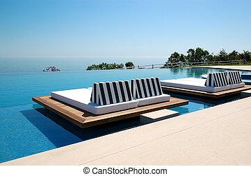 Una piscina infinita por playa en el hotel de lujo moderno, Pieria, Grecia