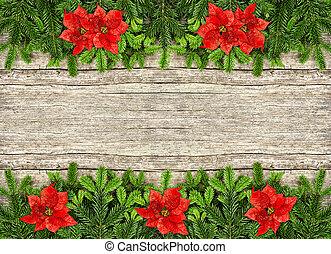 Una rama de árbol de Navidad y flores de poinsettia rojas