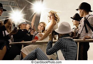 Una rubia hermosa que parece una superestrella posando y un montón de fotógrafos alrededor de ella tomando fotos