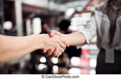 Una sección media de jóvenes mujeres de negocios, estrechando la mano.