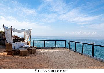 Una silla de cubierta junto al mar en un hotel en la India del estado de Kerala