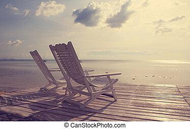 Una silla de playa blanca de madera frente al mar, efecto del filtro de la venta