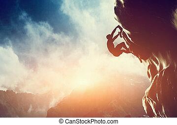 Una silueta de hombre escalando en roca, montaña al atardecer.