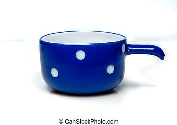 Una taza azul con lunares blancos
