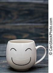 Una taza blanca con cara sonriente en una mesa de madera azul