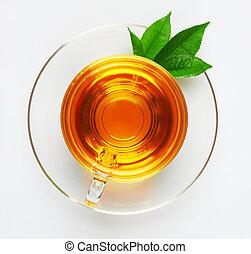 Una taza con té y hojas verdes