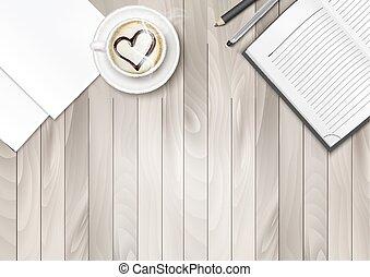 Una taza de café con forma de corazón y cuaderno en un escritorio de madera.