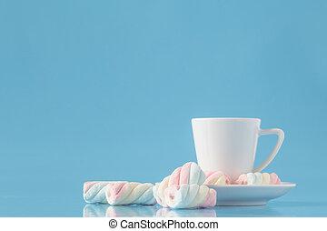Una taza de café expreso y malvavisco americano retorcido en azul
