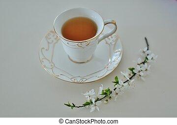 Una taza de té verde y flores