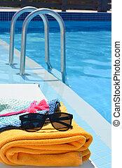 Una toalla de gafas de sol y un sombrero cerca de una piscina en un caluroso día de verano