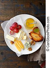 Una variedad de quesos rebanados en el plato