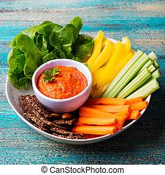 Una variedad de vegetales frescos con salsa. Comida saludable. Salsa de pimienta asada, extendida. Trasfondo de madera.