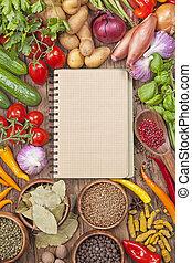 Una variedad de verduras frescas y un libro de recetas en blanco