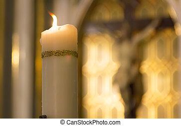 Una vela blanca decorada ardiendo dentro de un católico con la imagen de Cristo detrás de la Iglesia