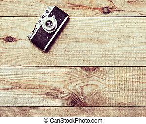 Una vieja cámara de filmación en el fondo de madera marrón.