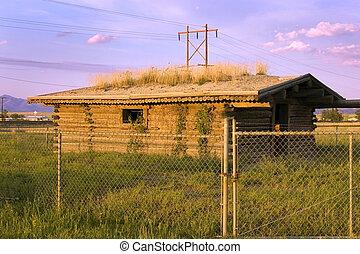 Una vieja casa de pinoe tras las vallas