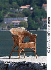 Una vieja silla de mimbre en el fondo de la bahía marina. Primer plano