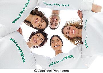 Una vista baja de gente con camisetas voluntarias