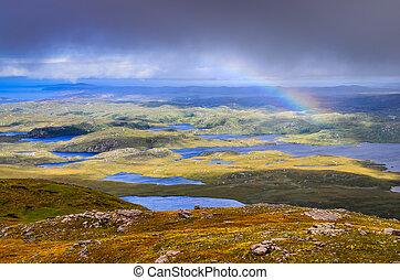 Una vista escénica de hermosos lagos, nubes y arco iris en el área de Inverpolly, las tierras altas de Escocia, el Reino Unido