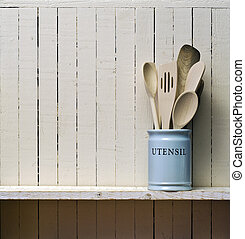 Utensilios de cocina de cocina, espátulas de madera, etc. en la vajilla de porcelana, en el estante de madera contra la pared rústica de la cocina; excelente espacio de copia sobre la pared