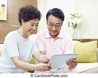 utilizar, tableta, juntos, computadora, asiático, pareja mayor