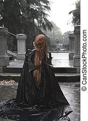Vampiro, belleza oscura bajo la lluvia, mujer pelirroja con abrigo largo y negro