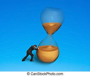 Varón empujando el reloj de arena